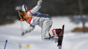 Chloe Kim doing in an aerial trick during a snowboarding competition