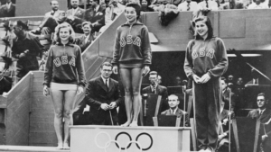 Vicki Draves stands on a podium with two other U.S. divers