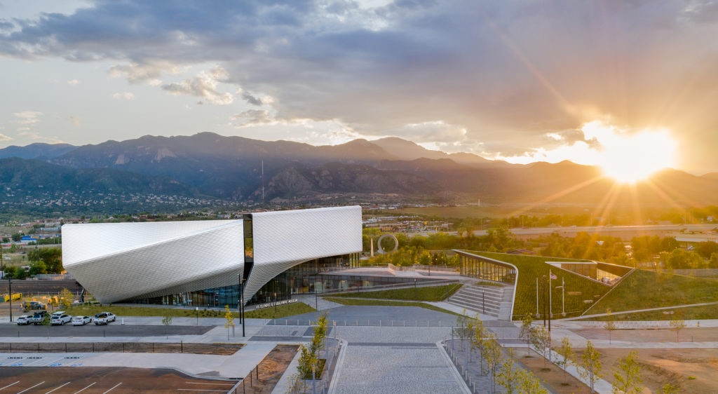 The sun sets over the mountains behind the exterior of the United States Olympic and Paralympic Museum.
