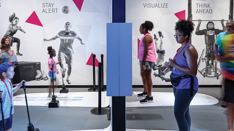 Guests using the interactive exhibits in the Athlete Training gallery