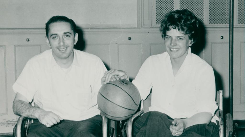 Saul and Christa Welger pose together holding a basketall